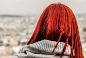 Girl with flaming red hair looking out over Paris