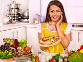 Woman cooking pizza at kitchen.