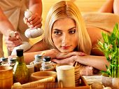 Blond woman getting herbal ball massage in spa.