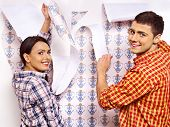 Happy family glues wallpaper at home.