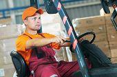warehouse worker driver in uniform operating forklift stacker loader