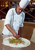 One arab chef baker in white uniform making pizza at kitchen