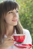 Young Adult Caucasian Girl Dreaming Near Window With Cup Of Tea Or Coffee.
