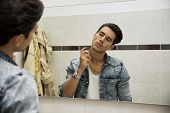 Handsome young man in bathroom, spraying cologne or perfume
