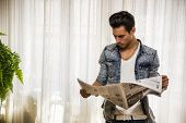 Handsome young man at home reading newspaper