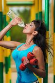 Portrait of cheerful young attractive woman drinking water outdoor