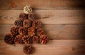 A group of pine cones arranged in a Christmas Tree shape on a rustic wood floor, Horizontal format w