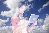 Double exposure of clouds and a businesswoman using her tablet