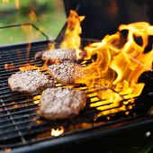 hamburgers being grilled with flames