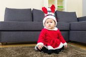 Baby girl with x mas dressing and seating on carpet