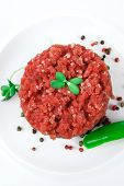 very big raw hamburger cutlet with sprouts and chilli pepper on white plate isolated over white back