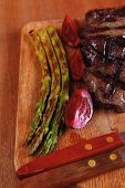 grilled beef pork meat steak fillet with asparagus  hot red peppers and cutlery on wooden cutting pl