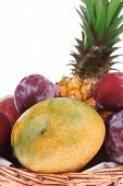 diet food - set of lot of tropical fruits include pineapple plum and mango in small basket isolated