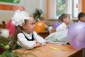 First grader girl in the first day of school in the classroom. Russia.