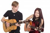 Singing musicians with guitars. Interracial young couple, Asian woman and Caucasian man.