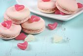 Pink Macarons With Pink And White Jelly Candy Hearts On Vintage Blue Table - Close Up.