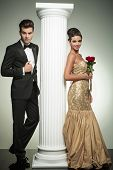 full body picture of an elegant couple near column, woman holding roses in her hand