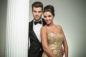 elegant fashion couple smiling together near column in studio
