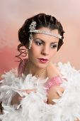 Beautiful vintage 1920s lady wearing a headband and white feather boa