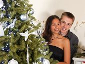 Decorated christmas tree and a young couple of different race