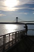 Fisherman is fishing near Varrazano-Narrows Bridge