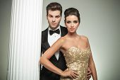 pic of evening gown  - fashion elegant couple man in tuxedo and woman in evening gown standing embraced near column in studio - JPG