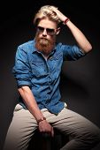 Picture of a fashion man in blue shirt wearing sunglasses sitting and looking away. On black backgro