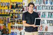 Portrait of confident young man showing digital tablet in hardware store