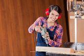 Portrait of confident female carpenter using drill machine on wood in workshop