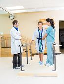 Physical therapists assisting female patient in walking with the support of bars