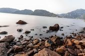 Stones on a background of blurred sea with mountain views