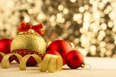 Christmas Bright red baubles with golden ribbons on bokeh background