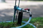 Water Valve With Hose In Garden At Morning