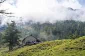 LA GIETE, SWITZERLAND - AUGUST 31: Refuge with misty forest on mountain in the background. The refuge is on a stage of the popular Mont Blanc tour. August 31, 2014 in La Giete.