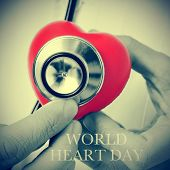 closeup of a doctor auscultating a red heart with a stethoscope and the text world heart day