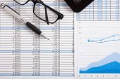 Business scene: calculator, pen and eyeglasses over business documents