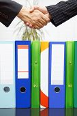 Woman And Man Are Handshaking Over Binders, Handing Business Concept