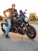 Biker Man Wearing A Leather Jacket Sitting On His Motorcycle Outdoors