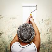 tan athletic man paints the wall - view from the back