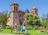 CUZCO, PERU, MAY 1, 2014:  Elderly tourist rests on bench with his daughter in front of the Cathedra