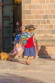 CUZCO, PERU, MAY 1, 2014:elderly souvenirs seller walks down the street