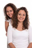 Real twin sisters: Portrait of two smiling isolated young woman with natural curls.