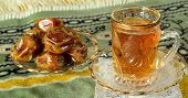 Hot tea with dates on a carpet.