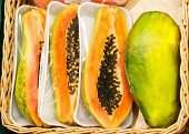 foto of papaya fruit  - Half cut and whole papaya fruits  in shop - JPG