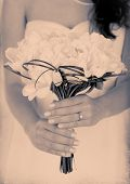 Bride holding wedding bouquet of white peonies in shades of grey