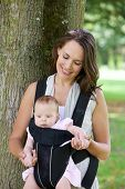 Happy Mother With Baby In Sling