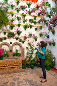 Woman is watering the flowers on  wall, Cordoba Patio Fest, Spain - 10 of May, 2013