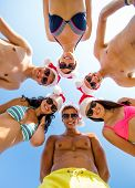 friendship, christmas, summer vacation, holidays and people concept - group of smiling friends weari