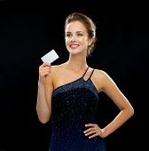 wealth, money, luxury and people concept - smiling woman in evening dress holding credit card over b
