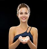 people, holidays and glamour concept - smiling woman in evening dress over black background